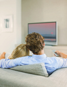 Couple watching television on sofa - CAIF04588
