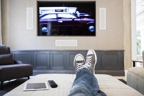 Woman's feet on ottoman watching TV - HOXF00187