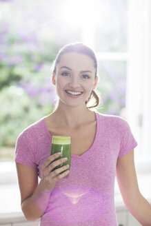 Portrait smiling woman drinking green smoothie - HOXF00193