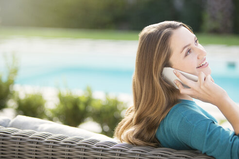 Brunette woman talking on cell phone at poolside - HOXF00205