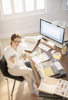 Interior designer examining swatches at desk in home office - HOXF00208