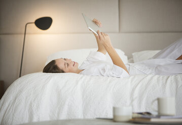 Woman in bathrobe laying on bed using digital tablet - HOXF00211