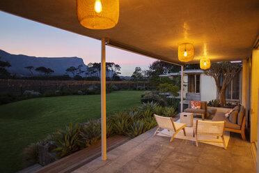 Illuminated patio overlooking mountains at dusk - HOXF00232