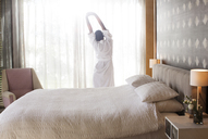 Woman in bathrobe stretching with arms raised in bedroom - HOXF00268