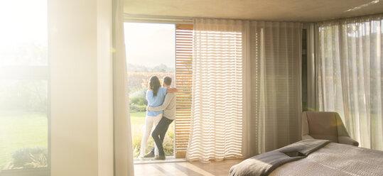 Couple hugging at patio doorway in bedroom - HOXF00271