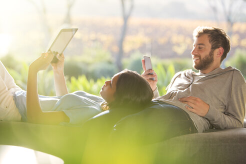 Couple laying and using digital tablet and cell phone on sunny patio - HOXF00274