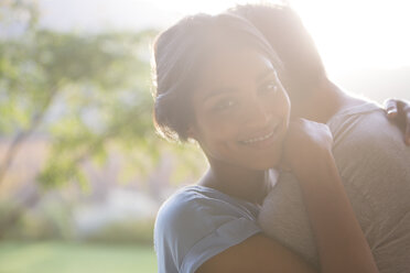 Portrait smiling woman hugging man outdoors - HOXF00286