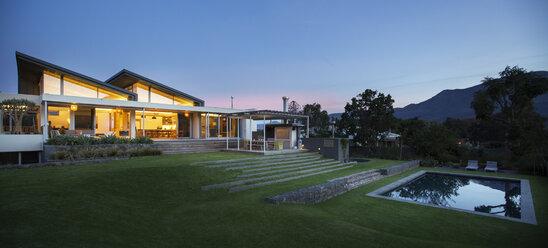 Illuminated modern house beyond yard and swimming pool at night - HOXF00289