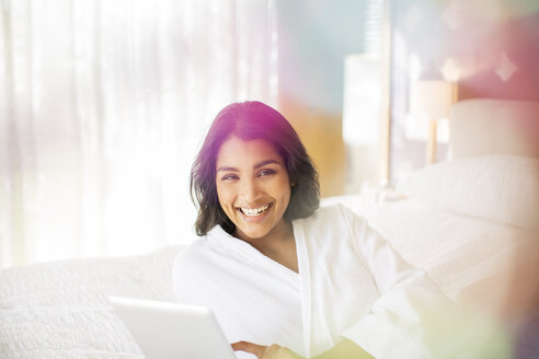 Portrait smiling woman in bathrobe using digital tablet on bed - HOXF00292