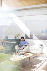 Woman reading magazine in sunny living room - HOXF00316