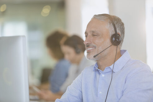 Businessman with headset working at computer in office - HOXF00400