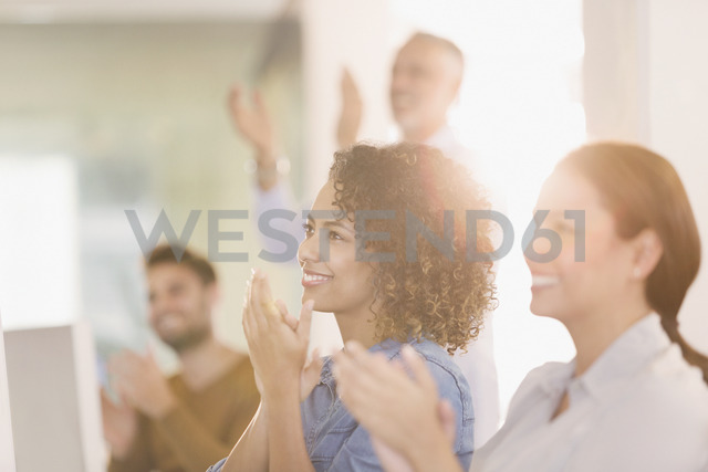 Businesswomen clapping in office - HOXF00415