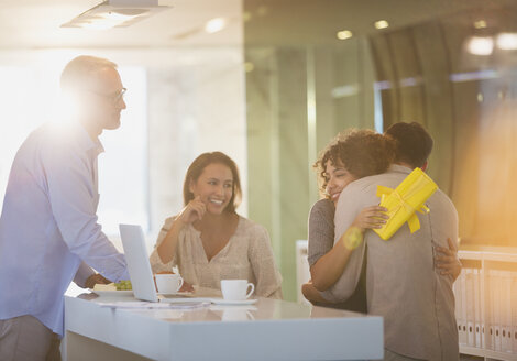 Business people giving gift to businesswoman in office - HOXF00427
