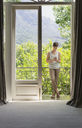 Woman texting with cell phone on luxury balcony - HOXF00439