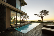 Modern luxury home showcase patio and swimming pool with sunset ocean view - HOXF00490