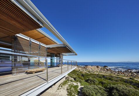 Modern luxury home showcase with ocean view under sunny blue sky - HOXF00496