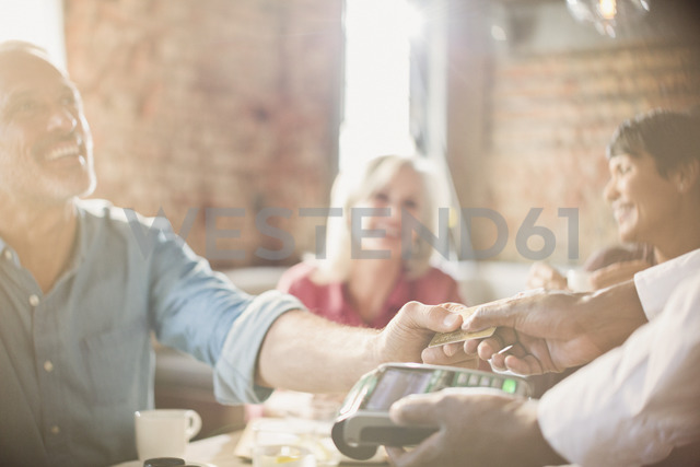 Customer paying waiter with credit card at restaurant table - HOXF00517
