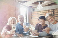 Portrait smiling couples toasting white wine glasses at restaurant table - HOXF00520