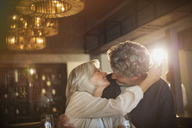 Senior couple hugging and kissing in bar - HOXF00523