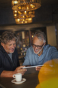 Men using digital tablet and drinking coffee at restaurant table - HOXF00541