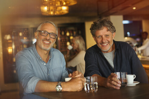 Portrait smiling men drinking coffee and water at restaurant table - HOXF00544