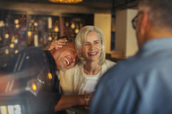 Affectionate senior couple laughing and hugging in bar - HOXF00553