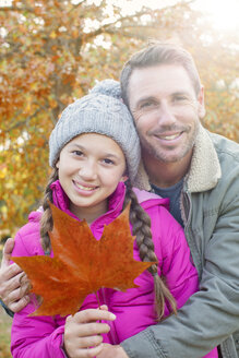 Portrait father and daughter with autumn leaf hugging - HOXF00574