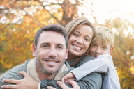 Portrait smiling family hugging in front of autumn leaves - HOXF00577