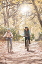 Mother and daughter bike riding on path in woods - HOXF00580