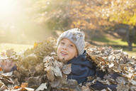 Portrait smiling boys covered in autumn leaves - HOXF00583