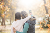 Affectionate mother and daughter taking selfie outdoors - HOXF00595