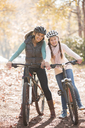 Portrait smiling mother and daughter on mountain bikes in woods - HOXF00601
