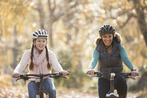Smiling mother and daughter bike riding outdoors - HOXF00610