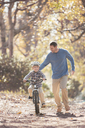 Father teaching son to ride a bicycle on path in woods - HOXF00616