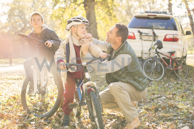 Father fastening helmet of son on bicycle in autumn woods - HOXF00619