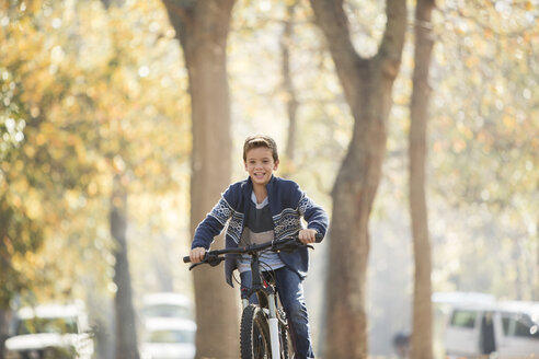 Smiling boy bike riding in park - HOXF00622