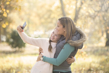 Mother and daughter taking selfie outdoors - HOXF00625