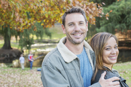 Portrait smiling couple at autumn park - HOXF00628
