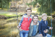 Portrait smiling father and sons with fishing rods - HOXF00637