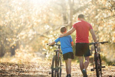 Affectionate father and son walking mountain bikes on path in woods - HOXF00646