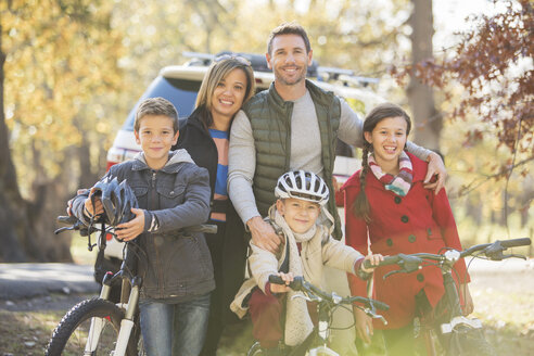 Portrait smiling family with bicycles outdoors - HOXF00649