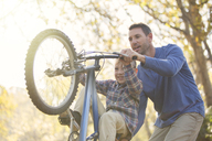 Father teaching son wheelie on bicycle - HOXF00658