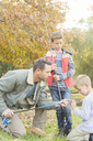 Father teaching sons to prepare fishing rods - HOXF00661