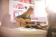 Teenage girls playing guitar and using digital tablet on bed - HOXF00685
