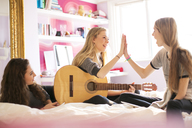 Teenage girls with guitar high fiving on bed - HOXF00691