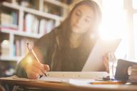 Teenage girl with digital tablet doing homework at sunny desk - HOXF00697