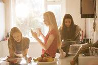 Teenage girls reading magazine, texting and using digital tablet in kitchen - HOXF00703