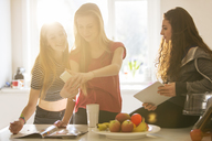 Teenage girls taking selfie with camera phone in kitchen - HOXF00706