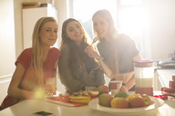 Portrait teenage girls eating in sunny kitchen - HOXF00709