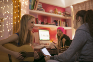 Teenage girls playing guitar and using digital tablet in bedroom - HOXF00712